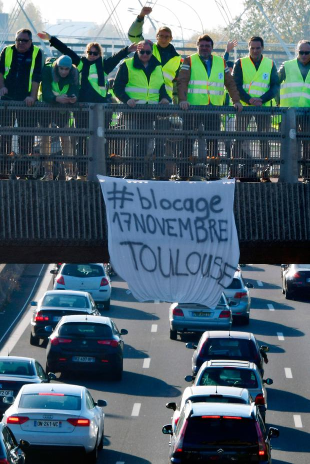 People demonstrate on a bridge and slow the traffic on a motorway in Toulouse (Photo by PASCAL PAVANI / AFP)PASCAL PAVANI/AFP/Getty Images