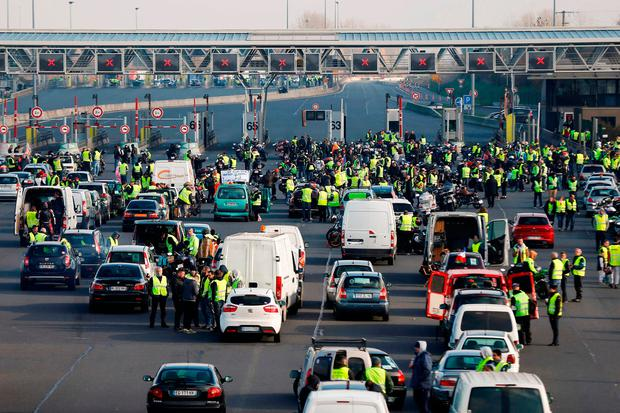 Demonstrators wearing Yellow Vests block the traffic during a protest against the rising of the fuel and oil prices on the A13 highway in Dozule, northwestern France. Photo: AFP/Getty
