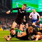 Jacob Stockdale goes over to score the only try of the game despite the efforts of Damian McKenzie and Aaron Smith. Photo: Ramsey Cardy/Sportsfile