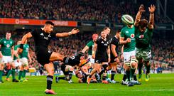 Substitute Luke McGrath attempts to block a kick from Richie Mo'unga as Ireland's bench found themselves defending the lead late on. Photo: Ramsey Cardy/Sportsfile
