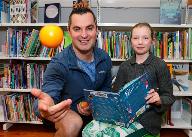 Apple a day: Personal trainer Karl Henry meets Siena Bowie Stokes (9), a pupil at St Catherine's National School in Donore, Dublin, at the launch of Healthy Ireland at Your Library. Photo: Damien Eagers