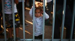 Hunger: A migrant girl waits to receive food in a temporary shelter. Photo: REUTERS/Hannah McKay