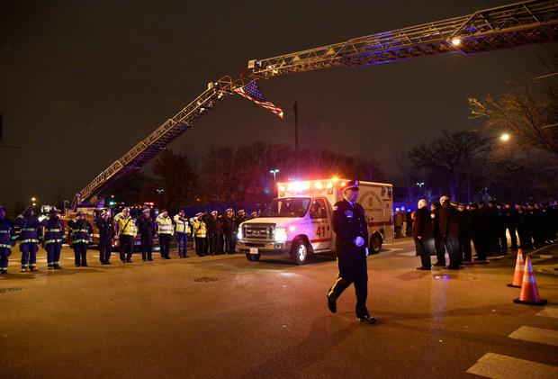 Chicago police officers and firefighters form an honor guard as the body of Chicago Police Officer Samuel Jimenez is brought to the coroner Monday, Nov. 19, 2018, in Chicago. A gunman opened fire Monday at a Chicago hospital, killing the police officer and a few hospital employees in an attack that began with a domestic dispute and exploded into a firefight with law enforcement inside the medical center. The suspect was also dead, authorities said. (AP Photo/David Banks)