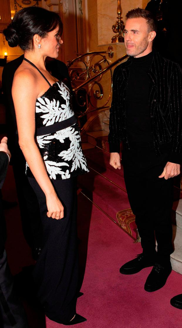 Meghan, Duchess of Sussex (L) greets British singer-songwriter Gary Barlow, as she attends the annual Royal Variety Performance at the Palladium Theatre in central London on November 19, 2018. (Photo by Ian Vogler / various sources / AFP)