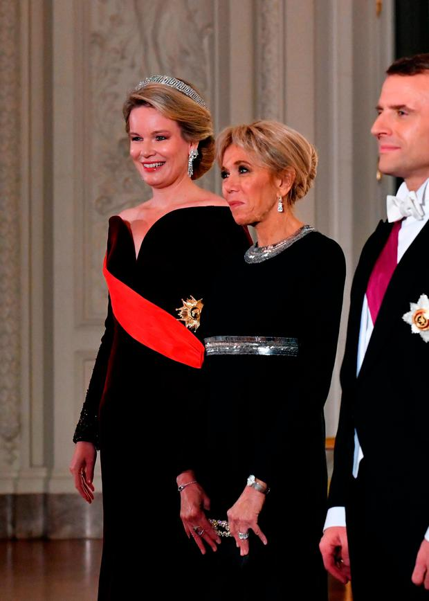 Belgium's Queen Mathilde (L) and French President's wife Brigitte Macron welcome guests for a state dinner at the Royal Palace in Laeken, Belgium on November 19, 2018, during a two-day state visit of the French President. (Photo by Geert VANDEN WIJNGAAERT / POOL / AFP)