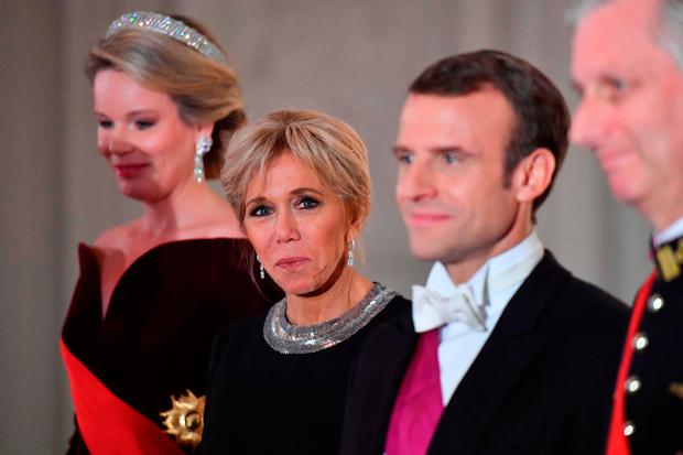 French President's wife Brigitte Macron (2L) stands next to her husband French President Emmanuel Macron (R) as they together with Belgium's royal couple welcome guests for a state dinner at the Royal Palace in Laeken, Belgium on November 19, 2018, during a two-day state visit of the French President. (Photo by EMMANUEL DUNAND / AFP)