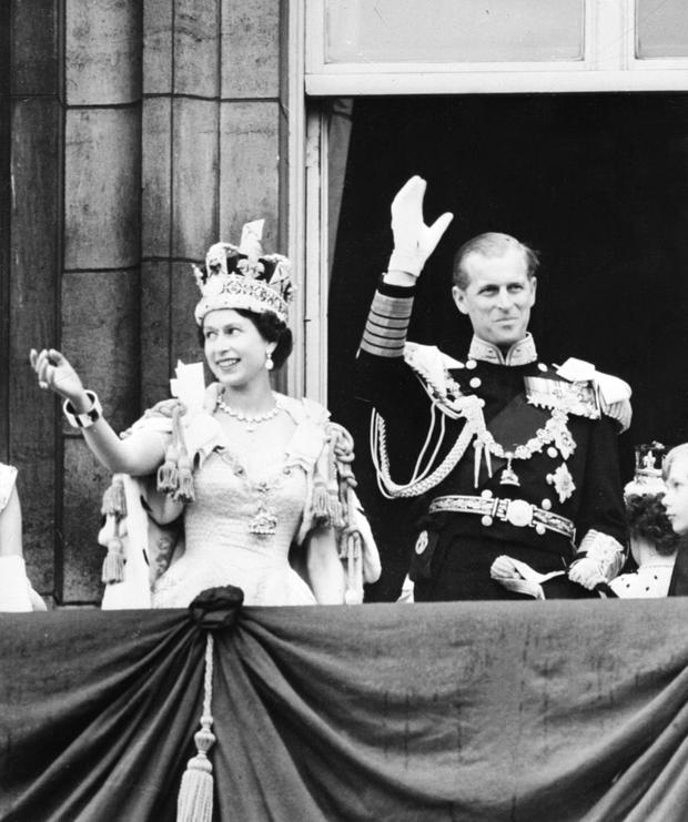 Britain's Queen Elizabeth II (L) accompanied by Britain's Prince Philip, Duke of Edinburgh (R) waves to the crowd, June 2, 1953 after being crowned at Westminter Abbey in London. - Elizabeth married the Duke of Edinburgh on the 20th of November 1947 and was proclaimed Queen in 1952 at age 25. Her coronation was the first worldwide televised event. (Photo by - / INTERCONTINENTALE / AFP)