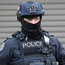 Arrests: A police officer at the scene of a raid in a Melbourne suburb