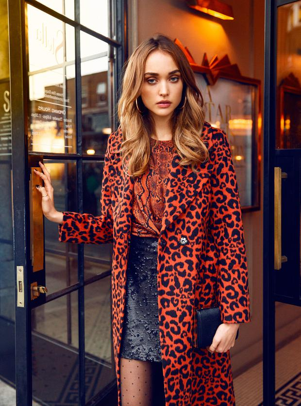 Leopard Belted Trench Coat €50, Snake Print Blouse €13, Black Brushed Sequin Skirt €16, Spot Tights €3.50, Star Detail Ankle Boots €23, Black and Gold Clutch Bag €12, Gold Chunky Hoop Earrings €3. Photo: Eilish McCormick