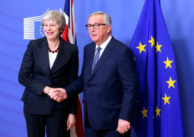 Meet: Theresa May shakes hands with European Commission President Jean-Claude Juncker. Photo: Francois Walschaerts/Reuters