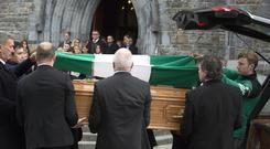 Farewell to Weeshie: Kerry footballer James O'Donoghue places The Legion flag on GAA broadcaster Weeshie Fogarty's coffin at his funeral in St. Mary's Cathedral, Killarney yesterday. Photo: Don MacMonagle
