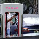 A man finishes charging his Tesla car at a charging point outside Tesla China headquarters in Beijing, China July 11, 2018. REUTERS/Jason Lee/File Photo