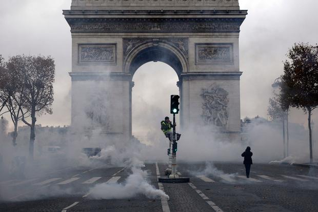 The Arc de Triomphe is pictured in a cloud of tear gas during clashes between demonstrators, called the yellow jackets, and riot police on the famed Champs-Elysees avenue, as they protest against the rising of the fuel taxes, in Paris, France, Saturday, Nov. 24, 2018. France is deploying thousands of police to try to contain nationwide protests and road blockades by drivers angry over rising fuel taxes and Emmanuel Macron's presidency. (AP Photo/Kamil Zihnioglu)