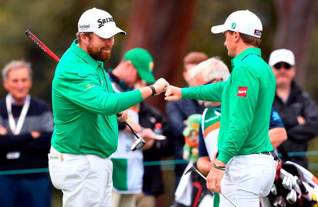 Shane Lowry (L) and Paul Dunne (R) of Ireland bump fists on the final day of the World Cup of Golf at the Metropolitan Golf Club in Melbourne on November 25, 2018. (Photo by William WEST / AFP)