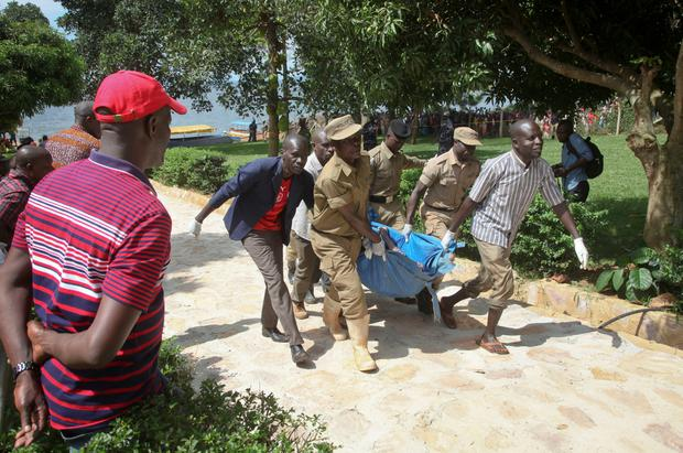 Ugandan police carry away a body of one of the victims of a boat which capsized in Lake Victoria near the capital, Kampala, Uganda, Sunday, Nov. 25, 2018. Police say dozens died when the boat, which was carrying more than 90 passengers on a pleasure cruise, capsized Saturday evening. (AP Photo/Stephen Wandera)