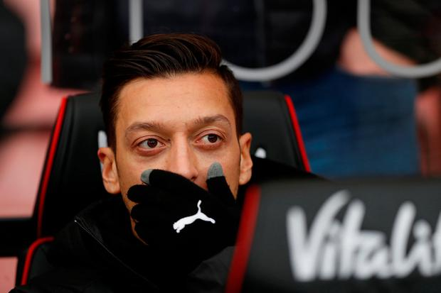Mesut Ozil watches on from the sideline