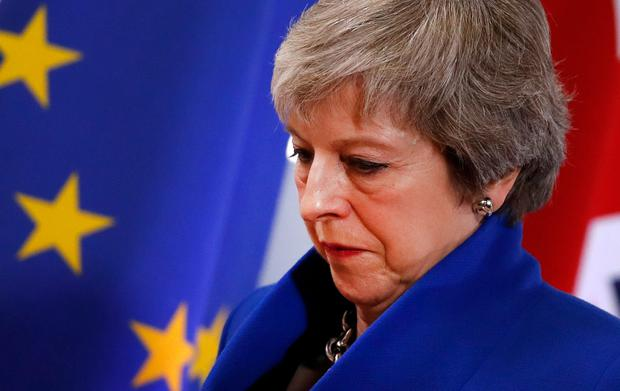 British Prime Minister Theresa May walks past the EU flag at the conclusion of an EU summit in Brussels, Sunday, Nov. 25, 2018. European Union leaders gathered Sunday to seal an agreement on Britain's departure from the bloc next year, the first time a member country will have left the 28-nation bloc. (AP Photo/Alastair Grant)