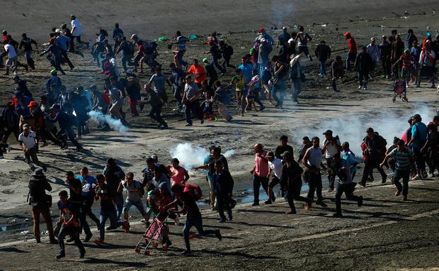 Fumes: Migrants run from tear gas fired by US border patrol near the border in Tijuana, Mexico. Photo; Reuters/Hannah McKay