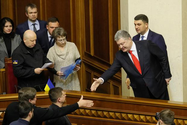 Ukrainian President Petro Poroshenko shakes hands with lawmakers after a vote on his proposal to introduce martial law REUTERS/Valentyn Ogirenko