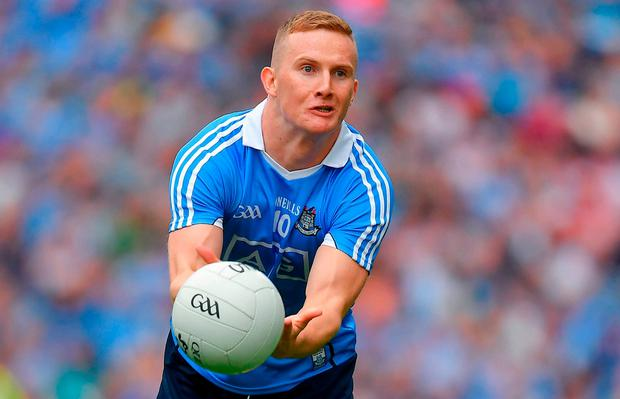 Ciarán Kilkenny handpasses the ball