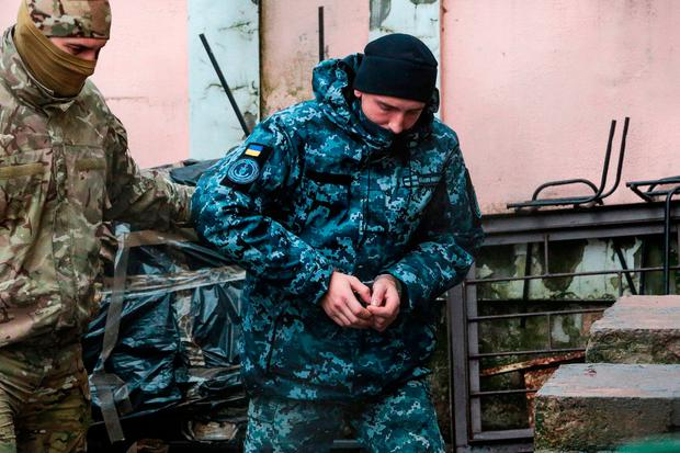 Detained crew: A member of Russia's FSB security service escorts a Ukrainian navy sailor before a court hearing in Crimea. Photo: STR/AFP/Getty Images