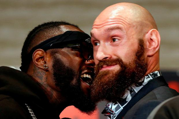 Boxers Deontay Wilder, left, and Tyson Fury exchange words as they face each other at a news conference in Los Angeles