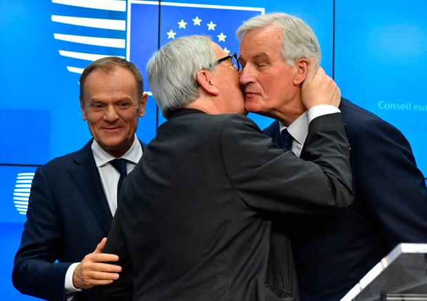 Sealed with a kiss: EC president Jean-Claude Juncker, centre, kisses EU chief Brexit negotiator Michel Barnier, right, as European Council president Donald Tusk looks on at the conclusion of an EU summit in Brussels. Photo: AP