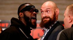Boxers Deontay Wilder, left, and Tyson Fury exchange words as they face each other at a news conference in Los Angeles. (AP Photo/Damian Dovarganes)
