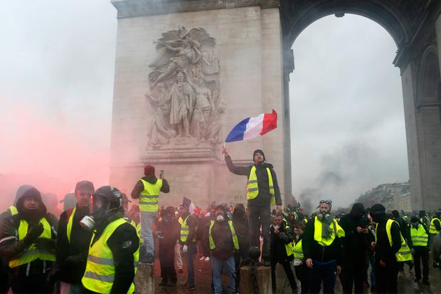 A demonstrator wearing a yellow jacket waves a French flag at the Arc de Triomphe during a demonstration in Paris (AP Photo/Thibault Camus)