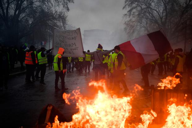Demonstrators carry a French flag during a protest of Yellow vests against rising oil prices and living costs (Photo by Alain JOCARD / AFP)ALAIN JOCARD/AFP/Getty Images