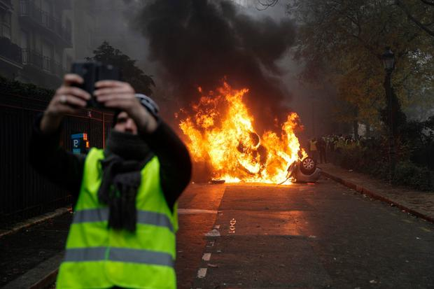 A man takes a selfie with a burning car in central Paris. Photo: Getty