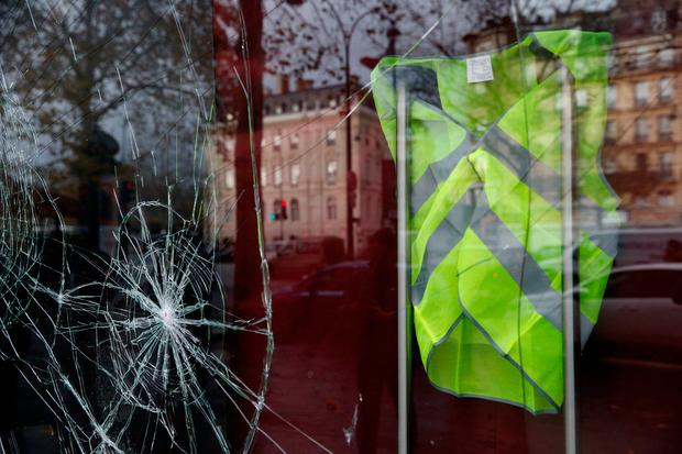 A yellow vest hangs inside a vandalized store front the morning after clashes with protesters wearing yellow vests, a symbol of a French drivers' protest against higher diesel fuel taxes, in Paris, France, December 2, 2018. REUTERS/Stephane Mahe