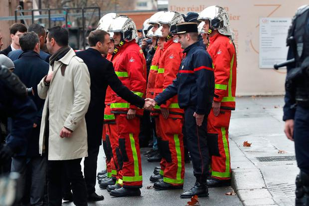 France's President Emmanuel Macron shakes hand with a firefighter as he visits firefighters and riot police officers the day after a demonstration, in Paris, France December 2, 2018. Thibault Camus/Pool via REUTERS