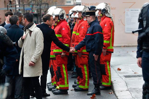 Thanks: President Emmanuel Macron visits firefighters and riot police officers in Paris yesterday. AP Photo/Thibault Camus
