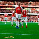 A banana thrown from the crowd is seen at the side of the pitch as Arsenal's Gabonese striker Pierre-Emerick Aubameyang (C) celebrates after scoring the opening goal from the penalty spot during the English Premier League football match between Arsenal and Tottenham Hotspur at the Emirates Stadium