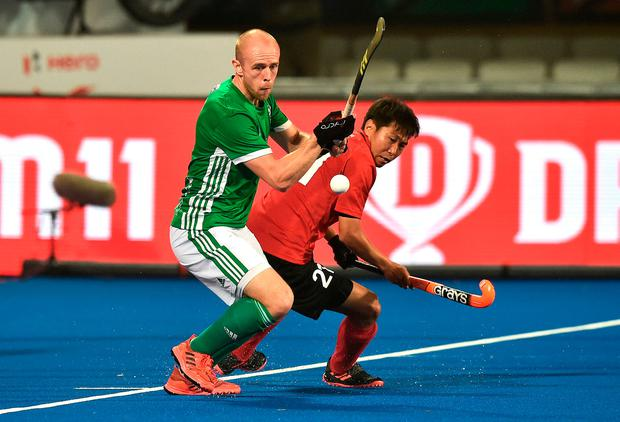 Eugene Magee and Chen Du of China battle for possession. Photo: Charles McQuillan/Getty Images for FIH