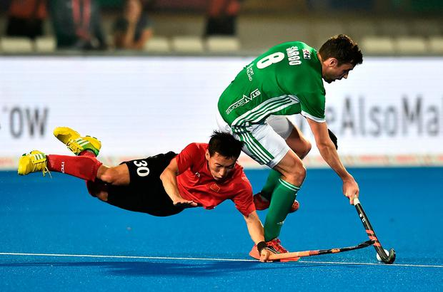 Chris Cargo brushes off a tackle from China's Weibao Ao. Photo: Charles McQuillan/Getty Images for FIH