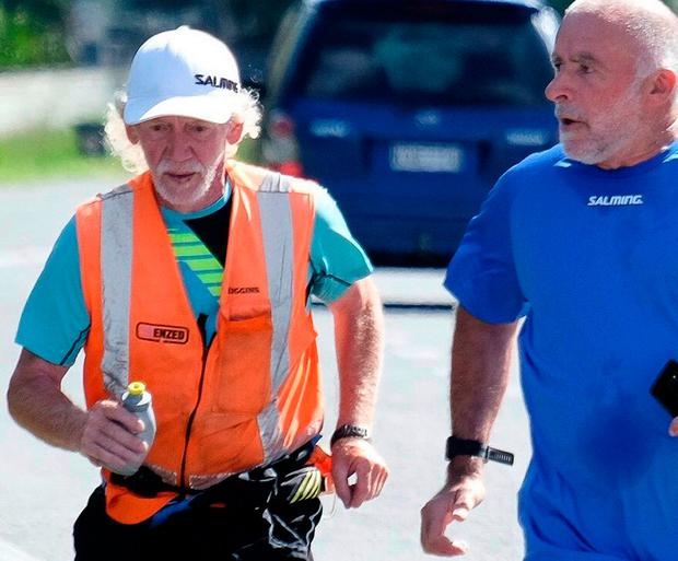 Perry Newburn, left, runs with support crew member Graeme Calder, right, on State Highway 1 near Raumati, New Zealand
