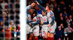 Roberto Firmino (hidden) celebrates with team mates after scoring Liverpool's second goal. Photo by Alex Livesey/Getty Images
