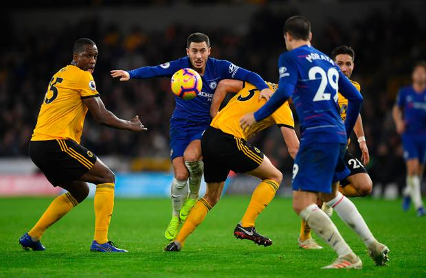 Eden Hazard of Chelsea battles for possession with Ryan Bennett and Willy Boly of Wolverhampton Wanderers on Wednesday.