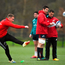 Rory Scannell takes a kick during training while Billy Holland and head coach Johann Van Graan consult their notes. Photo: Sportsfile