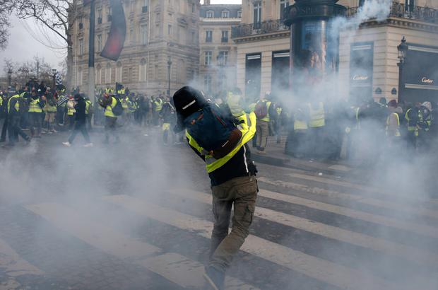 A demonstrator throws an item during scuffles near the Champs-Elysees avenue Saturday, Dec. 8, 2018 in Paris. Crowds of yellow-vested protesters angry at President Emmanuel Macron and France's high taxes tried to march Saturday on the presidential palace, surrounded by exceptional numbers of police bracing for outbreaks of violence after the worst rioting in Paris in decades. (AP Photo/Rafael Yaghobzadeh)