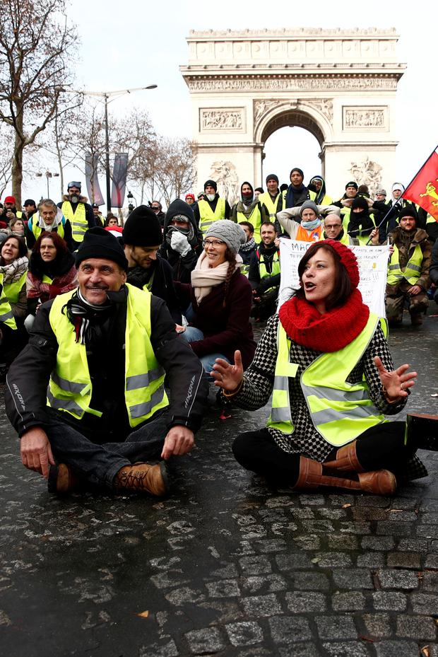 Protesters wearing yellow vests sit on the Champs-Elysees Avenue near the Arc de Triomphe during a national day of protest by the