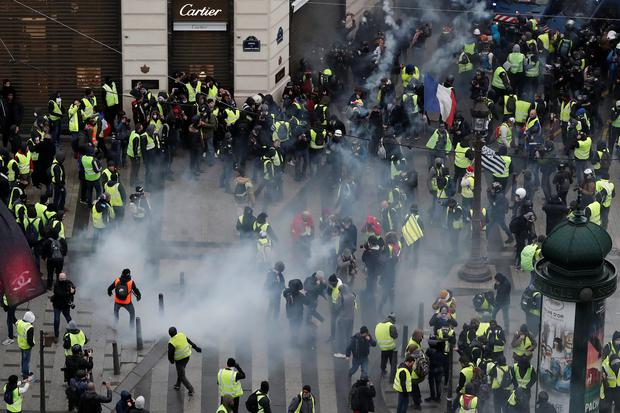 Tear gars floats in the air around protesters wearing yellow vests during clashes with French Gendarmes on the Champs-Elysees Avenue as part of a demonstration by the