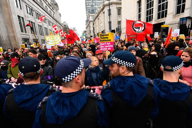Police officers monitor protesters in Trafalgar Square taking part in an anti-fascist counter-demonstration against a