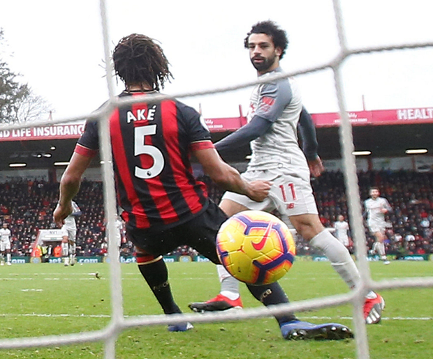 Salah days are back: The Liverpool striker scores the third goal of his hat-trick against Bournemouth on Saturday to help Liverpool go top of the Premier League