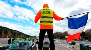 A protester with 'Macron clear off' written on his back at a motorway toll booth near Marseille. Photo: Sylvain Thomas/AFP/Getty