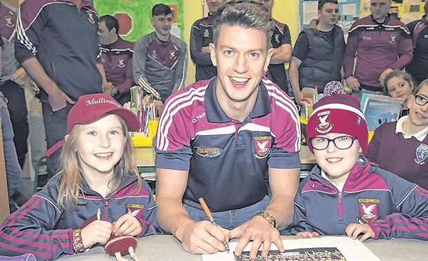 Keegan signs autographs for Shauna McGivney and Maria McHale at St Columba's National School yesterday. Photo: Colin O'Riordan/Sportsfile