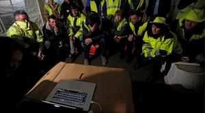 Angry: Protesters watch Macron's speech on a computer. Photo: Reuters