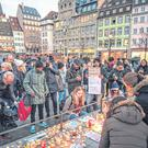 Tributes: People light candles at the Christmas market in Strasbourg where on Tuesday a man shot 14 people, killing at least two. Photo: Thomas Lohnes/Getty Images)